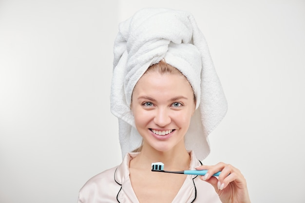 Cheerful young pretty woman with toothy smile holding toothbrush by her mouth while standing in isolation
