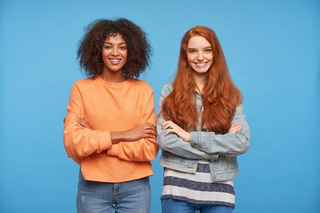青い壁に隔離された魅力的な笑顔で見ながら白い完璧な歯を見せてカジュアルな色の服を着た陽気な若いきれいな女性