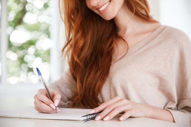 Веселая молодая рыжая дама, сидящая в классе, написание заметок.