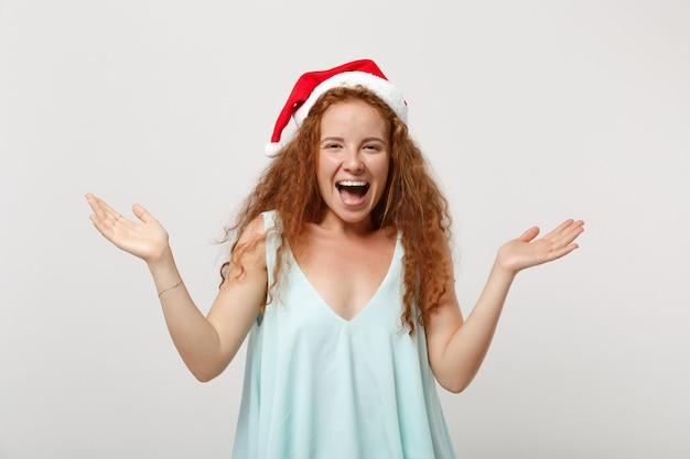 明るい服を着た陽気な若い赤毛のサンタの女の子、白い背景で隔離のクリスマス帽子、スタジオの肖像画。明けましておめでとうございます2020年のお祝いの休日のコンセプト。コピースペースをモックアップします。手を広げます。