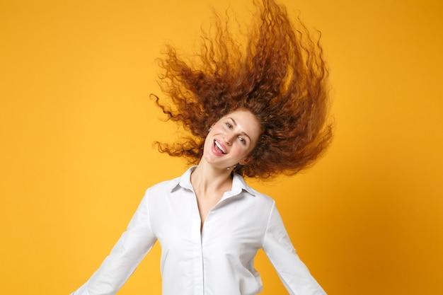 노란 오렌지 벽에 고립 된 흰 셔츠 포즈에 쾌활 한 젊은 빨간 머리 여자 소녀