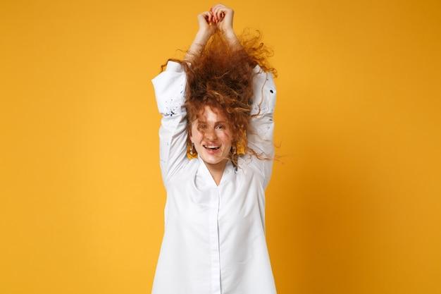 Веселая молодая рыжая девушка в белой рубашке позирует изолированной на желто-оранжевой стене