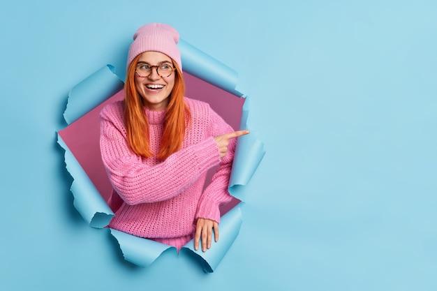 Веселая молодая рыжая женщина носит розовую шляпу и вязаный свитер, указывая на место для копирования из бумажной дыры