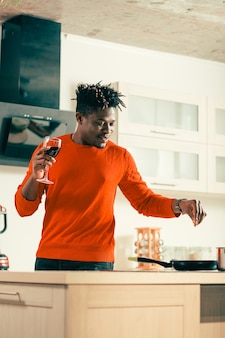 Веселый молодой расслабленный мужчина чувствует себя хорошо и улыбается, стоя на современной кухне с бокалом вина, добавляя соль в блюдо