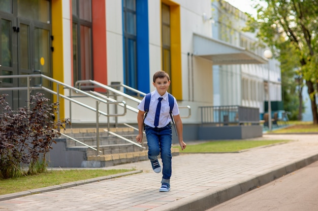 白いシャツ、青いネクタイ、バックパックで陽気な若い男子生徒が学校から実行されます。