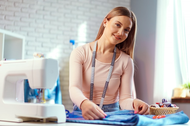 彼女のオフィスの作業テーブルに座っている陽気な若い女性の裁縫師