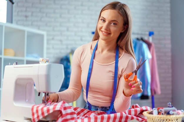 Cheerful young seamstress sitting at working table in her office