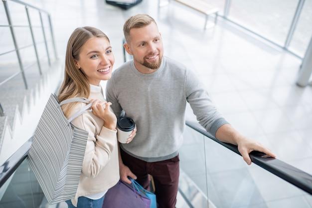 에스컬레이터에 서서 쇼핑하는 동안 위쪽으로 움직이는 동안 새로운 부서를보고 쾌활한 젊은 쇼핑객