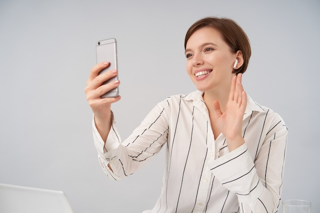 Cheerful young short haired brunette woman with natural makeup raising hand in hello gesture and smiling pleasantly while making video call with her smartphone, isolated on white