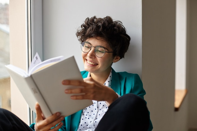 Cheerful young short haired curly brunette female in trendy elegant clothes reading book while sitting over big window, being in nice mood and smiling happily