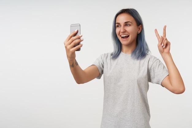 Allegra giovane signora dai capelli corti con tatuaggi alzando la mano con gesto di vittoria e sorridendo felicemente mentre fa il ritratto di se stessa su smartphone, isolato su bianco