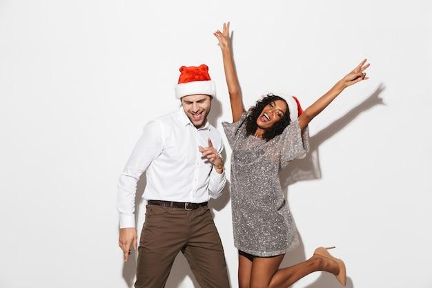 白いスペースで隔離の新年を祝う陽気な若いスマートな服装のカップル