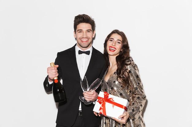 白で隔離された新年会を祝う陽気な若いスマートな服を着たカップル、プレゼントボックス、シャンパンとywoメガネを保持します。