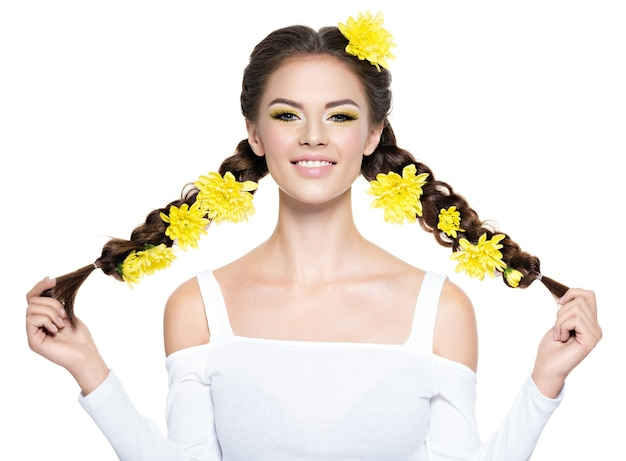 長いおさげ髪の陽気な若い笑顔の美しい女性。ファッションの肖像画。明るい黄色のメイクで魅力的な女の子-白で隔離。プロのメイク。アートヘアスタイル。