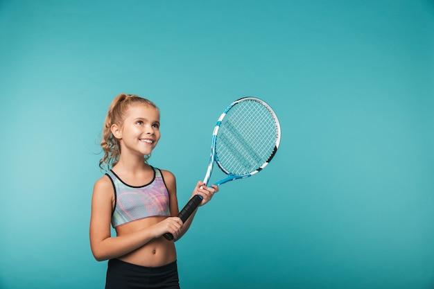 Веселая молодая спортивная девушка играет в теннис, изолированную над синей стеной