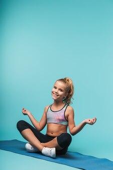 Веселая молодая спортивная девушка сидит на фитнес-коврике и делает упражнения йоги, изолированные на синей стене