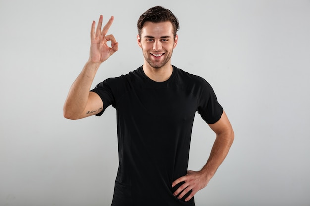 Cheerful young sports man posing showing ok gesture.