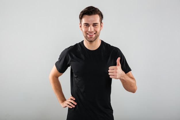 Cheerful young sports man posing showing thumbs up gesture.