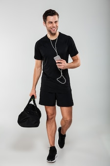 Cheerful young sports man using mobile phone listening music
