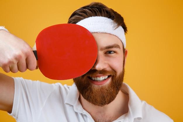 Веселый молодой спортсмен держит ракетку для настольного тенниса.
