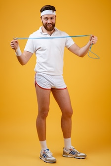 Cheerful young sportsman holding skipping rope