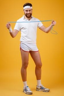 Веселый молодой спортсмен держит скакалку
