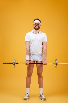 Cheerful young sportsman make sport exercises with barbell