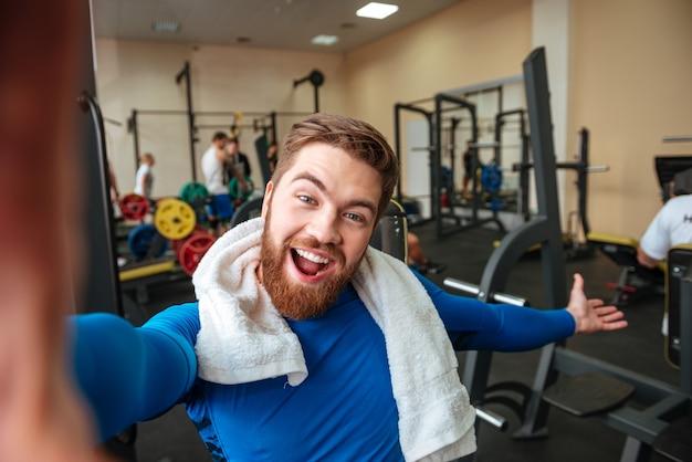 タオルで陽気な若いスポーツマンは、selfieを作ります。