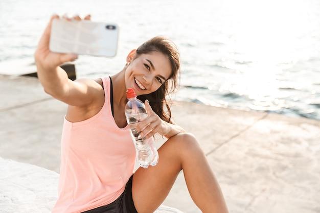 Веселая молодая спортсменка отдыхает после тренировки на пляже, делает селфи, пьет воду