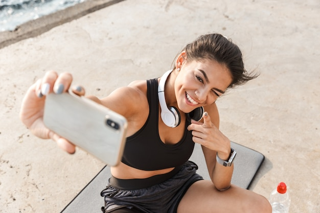 Cheerful young sportswoman resting after workout at the beach, taking a selfie, drinking water, sitting on a fitness mat
