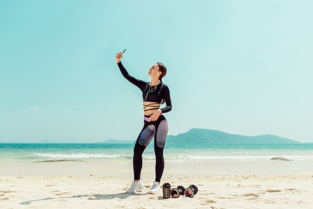 Cheerful young sportswoman with headphones taking a selfie with outstretched hands while standing at the beach. phuket. thailand. summer vacation and sport activity