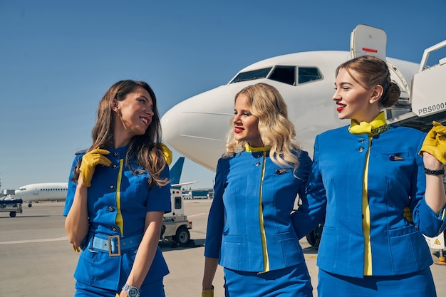 Cheerful young stewardess in stylish uniform smiling at her female colleagues