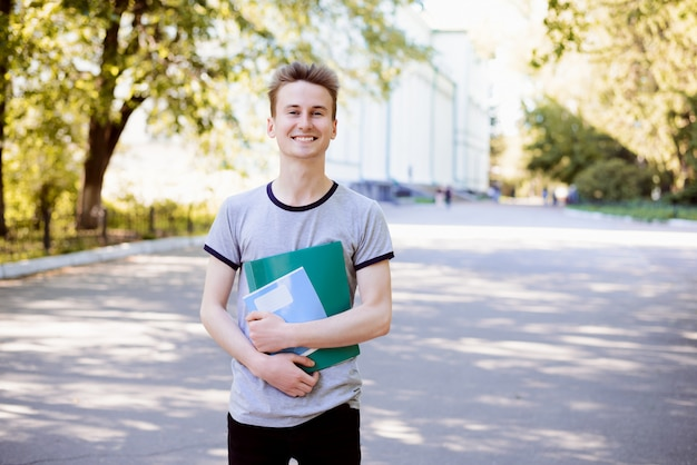 Cheerful young student with folder and exercise books in the park