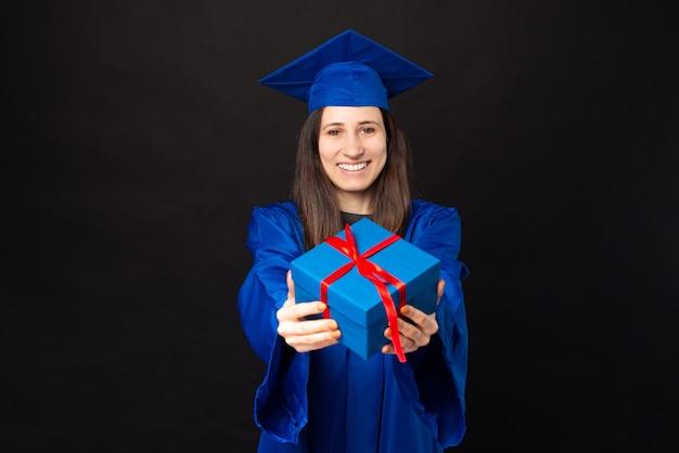 학사 및 졸업 모자 선물 상자를 들고 쾌활 한 젊은 학생 여자