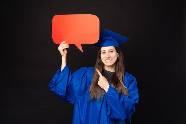 졸업 하 고 연설 거품을 가리키는 파란색 가운에 쾌활 한 젊은 학생 여자
