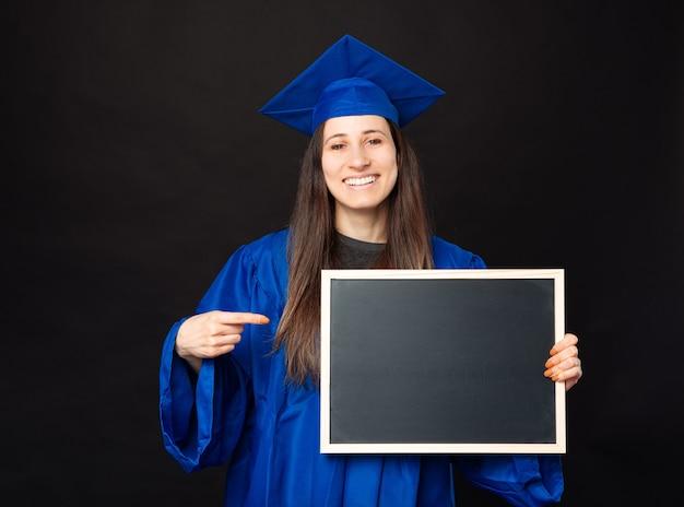 학사를 입고 검은 분필 보드를 가리키는 쾌활한 젊은 학생 여자