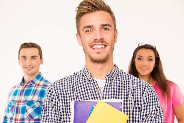 책과 자료를 들고 쾌활 한 젊은 학생