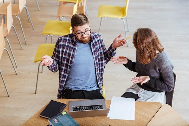 Веселые молодые студенты мужчина и женщина обсуждают проект