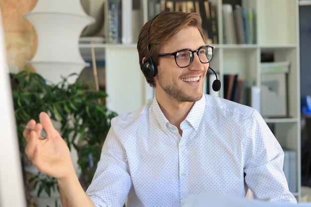 Жизнерадостный молодой оператор телефона поддержки мужского пола в гарнитуре, на рабочем месте при использовании компьютера, службы помощи и концепции центра обработки вызовов клиента.
