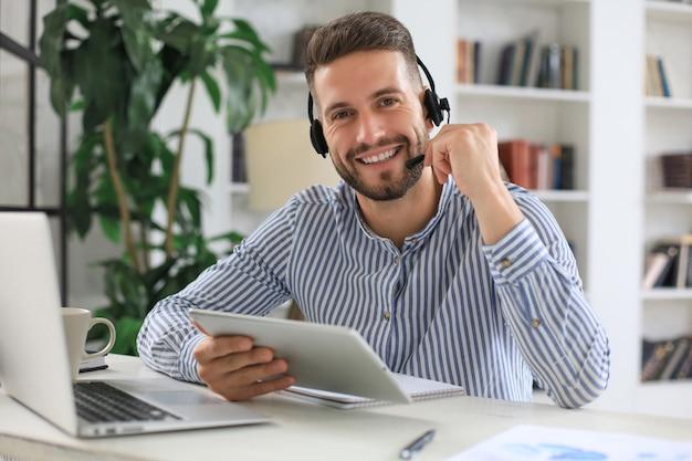 Жизнерадостный молодой оператор телефона поддержки мужского пола в гарнитуре, на рабочем месте при использовании цифрового планшета, службы помощи и концепции центра обработки вызовов клиента.