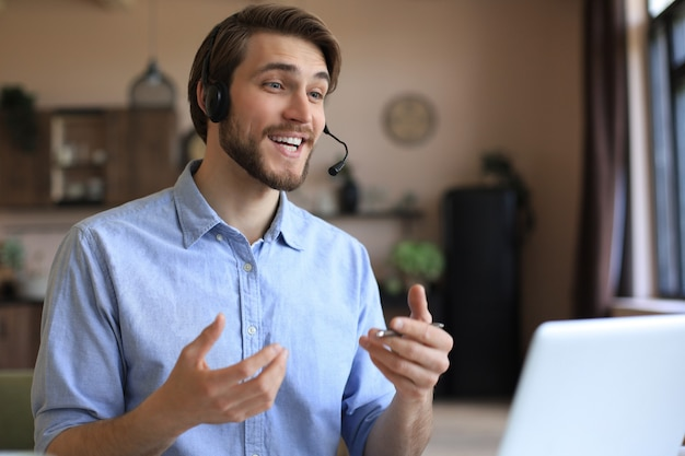 Жизнерадостный молодой оператор телефона поддержки мужского пола в гарнитуре, на рабочем месте при использовании компьтер-книжки, службы помощи и концепции центра обработки вызовов клиента.