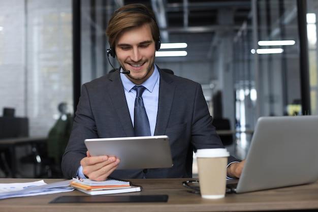 쾌활한 젊은 지원 전화 남성 교환원 헤드셋, 직장에서 노트북, 도움말 서비스 및 클라이언트 컨설팅 콜 센터 개념을 사용합니다.