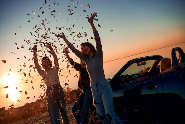 Веселые молодые три женщины танцуют возле кабриолета