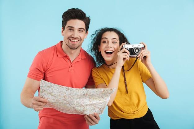 陽気な若い観光客のカップルが孤立して立って、地図を調べて、写真カメラを持っています