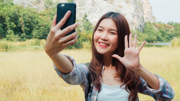 Cheerful young traveler asian lady with backpack selfie at mountain lake. korean girl happy using mobile phone taking selfie enjoy holidays on hiking adventure. lifestyle travel and relax concept.