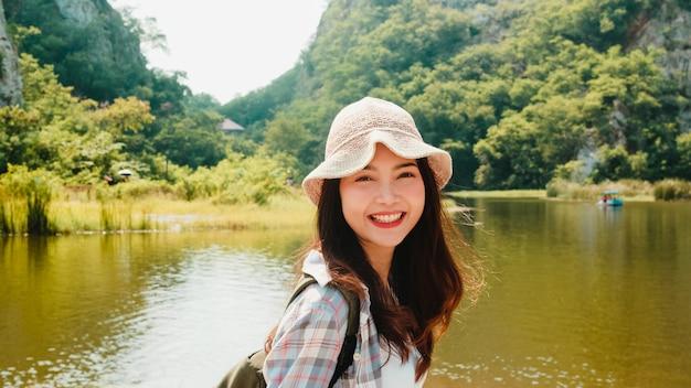 배낭에 산악 호수에서 걷고 쾌활 한 젊은 여행자 아시아 아가씨. 한국의 십대 소녀는 행복한 자유를 느끼는 휴가 모험을 즐깁니다. 라이프 스타일 여행 및 자유 시간 개념에서 휴식.