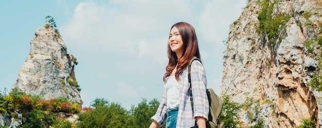 Cheerful young traveler asian lady with backpack walking at the mountain lake. korean teen girl enjoy her holidays adventure feeling happy freedom. lifestyle travel and relax in free time concept.