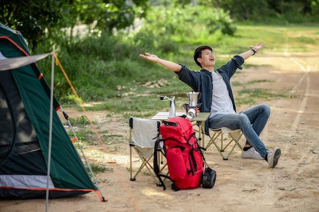夏休みのキャンプ旅行中にコーヒーセットと淹れたてのコーヒーグラインダーを作る森のテントの前に座っている陽気な若い旅行者の男