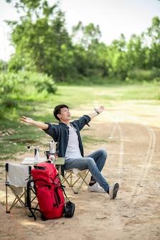 쾌활한 젊은 여행자는 여름 방학 동안 캠핑을 하는 동안 커피 세트와 신선한 커피 그라인더를 만드는 숲의 텐트 앞에 앉아