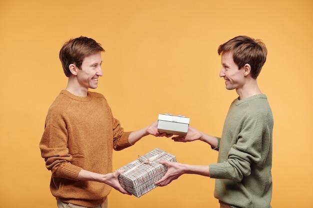 Веселые молодые близнецы в свитерах стоят на оранжевом фоне и обмениваются подарками, поздравляя друг друга с днем рождения